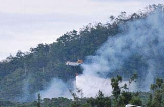 墜落現場で消火剤を撒く米軍ヘリ